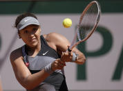 Japan's Naomi Osaka returns the ball to Romania's Patricia Maria Tig during their first round match of the French open tennis tournament at the Roland Garros stadium Sunday, May 30, 2021 in Paris. (AP Photo/Christophe Ena)