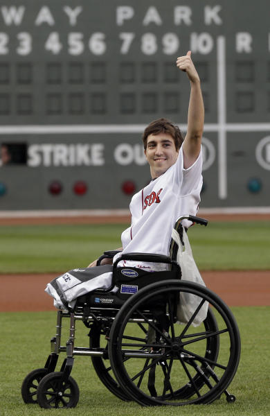 This May 28, 2013 file photo, Boston Marathon bombing survivor Jeff Bauman acknowledges cheering fans before throwing out a ceremonial first pitch at Fenway Park prior to a baseball between the Boston Red Sox and the Philadelphia Phillies in Boston. Bauman, who lost both legs in the Boston Marathon bombings, then helped authorities identify the suspects, is engaged and an expectant father. Bauman and his fiancé, Erin Hurley, tell The Associated Press that the baby is due July 14. They don't know if it's a boy or a girl, and they want it to be a surprise. The two were engaged in February. (AP Photo/Elise Amendola)