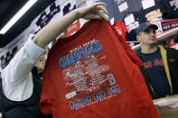 FILE - In this Oct. 29, 2007, file photo, a woman holds up a new Boston Red Sox 2007 World Series Champions tee-shirt at a souvenir shop near Fenway Park in Boston. Ballpark area businesses are struggling during the 2020 season while fans are not in attendance due to the COVID-19 pandemic. (AP Photo/Elise Amendola, File)