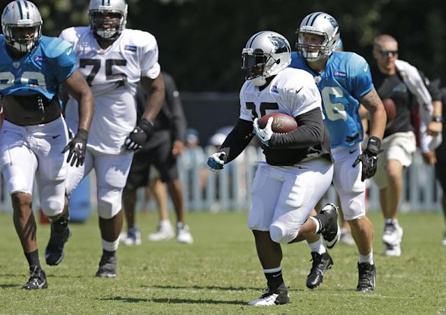 Carolina Panthers' Mike Tolbert (35) runs past the defense during an NFL football practice at their training camp in Spartanburg, S.C., Monday, July 28, 2014. (AP Photo/Chuck Burton)
