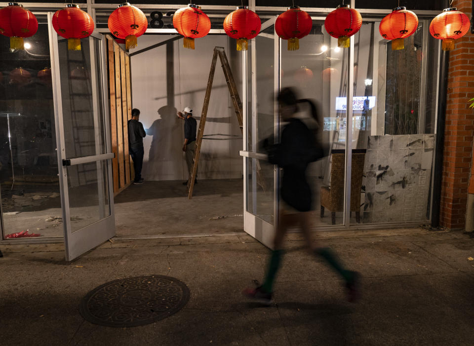A runner jogs past a former Chinese restaurant being converted into an artist space in the Chinatown district of Los Angeles, Thursday, Dec. 17, 2020. Bigotry toward Asian Americans and Asian food has spread steadily alongside the coronavirus in the United States. (AP Photo/Damian Dovarganes)