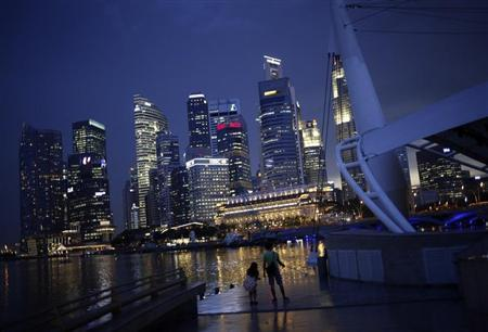 People take photos with the skyline of the financial district of Singapore in the background
