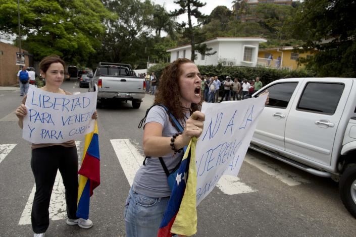 Demonstrators urge motorists to honk their horns during a protest near the Cuban embassy in Caracas, Venezuela, Tuesday, Feb. 25, 2014. Opponents of President Nicolas Maduro marched to the Cuban Embassy to protest what they consider the communist nation's interference in Venezuela's internal affairs. (AP Photo/Rodrigo Abd)