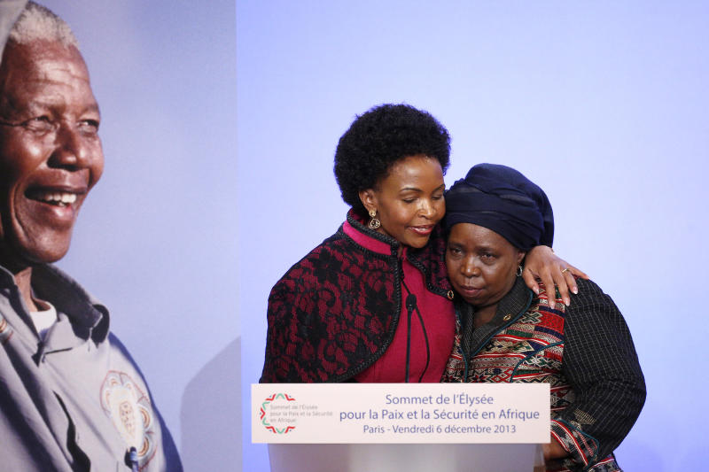 South African Minister for International Relations and Cooperation Maite Nkoana-Mashabane, left, embraces Chairperson of the African Union Commission Nkosazana Dlamini Zuma, next to the portrait of Nelson Mandela as part as the Elysee Summit for Peace and Security in Africa at the Elysee Palace, Friday, Dec.6, 2013 in Paris. France is hosting dozens of African leaders for a summit on security, just as the French military is launching an intervention in the Central African Republic and encouraging African governments to take more responsibility for peacemaking on the continent. As word of Mandela's death spread, current and former presidents, athletes and entertainers, and people around the world spoke about the life and legacy of the former South African leader.(AP Photo/Yoan Valat, Pool)