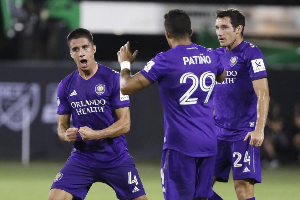 Orlando City defender Joao Moutinho (4) celebrates scoring a goal with teammates Orlando City forward Santiago Patino (29) and Orlando City defender Kyle Smith (24) during the second half of an MLS soccer match, Friday, July 31, 2020, in Orlando, Fla. (AP Photo/John Raoux)