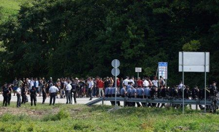 Migrants and Bosnian police are seen next to the border with Croatia in Velika Kladusa, picture taken from Maljevac, Croatia, June 18, 2018. REUTERS/Antonio Bronic