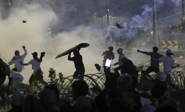 Supporters of the losing presidential candidate throw rocks towards police Wednesday, May 22, 2019, in Jakarta, Indonesia. Indonesian President Joko Widodo said authorities have the volatile situation in the country's capital under control after a number of people died Wednesday in riots by supporters of his losing rival in last month's presidential election. (AP Photo/Achmad Ibrahim)