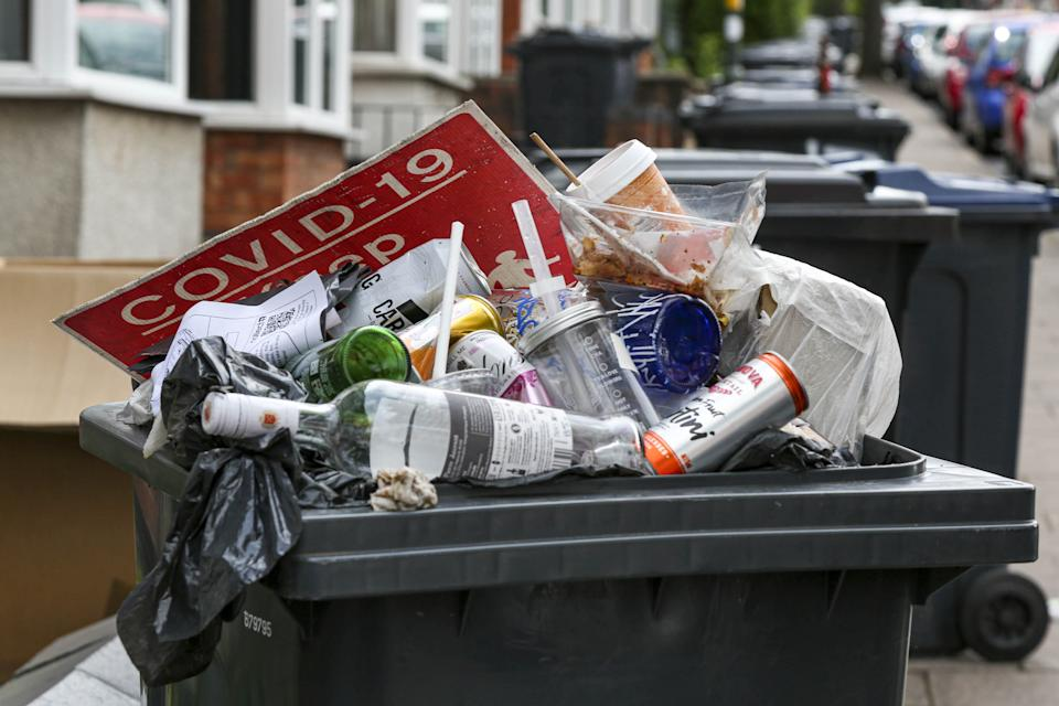 An overflowing bin with a Covid-19 sign on top in the build up of litter on Dawlish Road, Selly Oak, Birmingham. (SWNS)