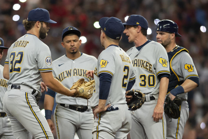 Milwaukee Brewers relief pitcher Daniel Norris (32) receives ball from manager Craig Counsell (30) during the sixth inning of a baseball game against the Atlanta Braves, Saturday, July 31, 2021, in Atlanta. (AP Photo/Hakim Wright Sr.)