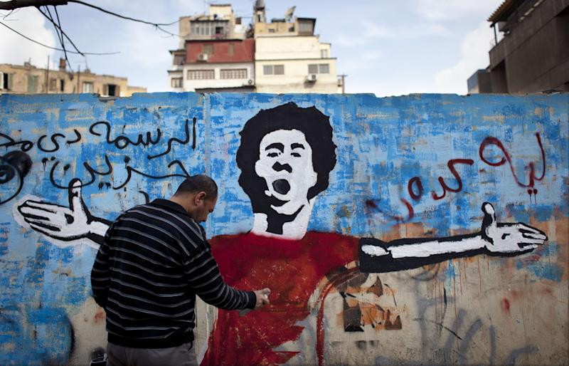 "An Egyptian activist paints a mural depicting a slain activist with Arabic that reads ""why did you do this? this is very sad,"" on a wall in Tahrir Square, Cairo, Egypt, Tuesday, Feb. 19, 2013. An ultraconservative Islamist adviser to Egypt's president resigned Monday in solidarity with a fellow aide who was fired amid allegations of abuse of office. (AP Photo/Nasser Nasser)"