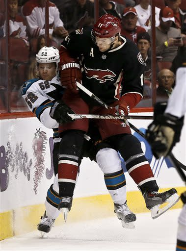 Phoenix Coyotes' Martin Hanzal, of the Czech Republic, checks San Jose Sharks' Matt Irwin (52) into the boards in the first period during an NHL hockey game, on Monday, April 15, 2013 in Glendale, Ariz. (AP Photo/Ross D. Franklin)