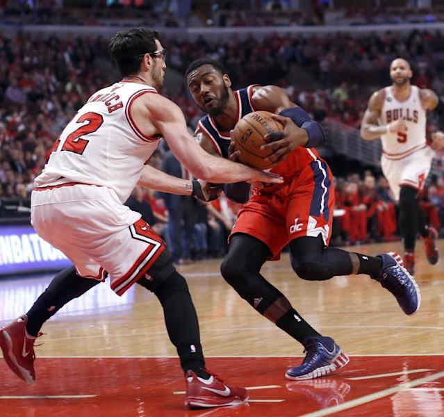Washington Wizards guard John Wall, right, drives on Chicago Bulls guard Kirk Hinrich (12) during the first half of Game 2 in an opening-round NBA basketball playoff series Tuesday, April 22, 2014, in Chicago. (AP Photo/Charles Rex Arbogast)