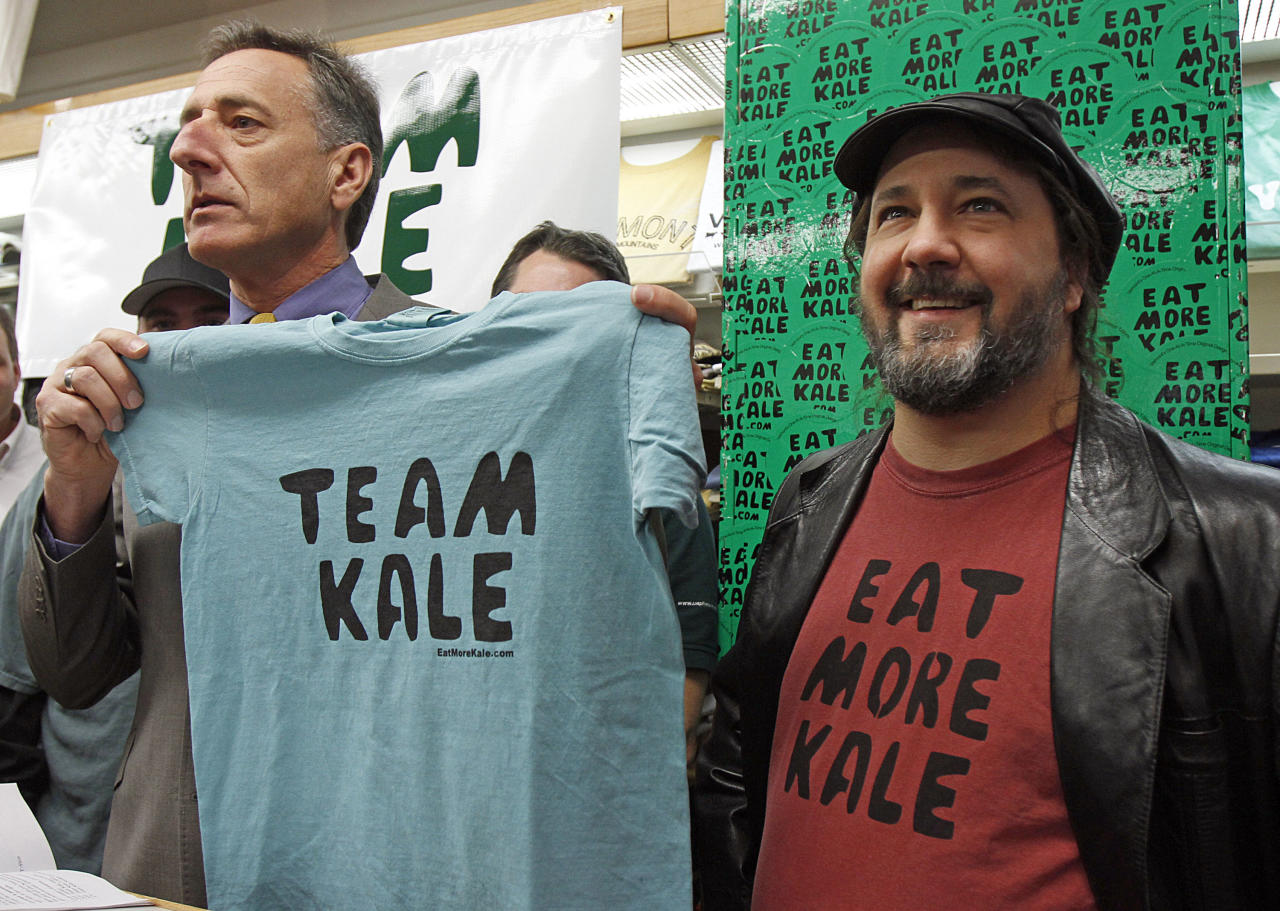 """Gov. Peter Shumlin, left, holds a Team Kale T-shirt during a news conference with Bo Muller-Moore in Montpelier, Vt., Monday, Dec. 5, 2011. Shumlin is throwing his support behind the Montpelier folk artist who has built his T-shirt business around the phrase """"eat more kale"""" and is engaged in a trademark fight with the second largest chicken restaurant chain in the country, Chick-fil-A. (AP Photo/Toby Talbot)"""