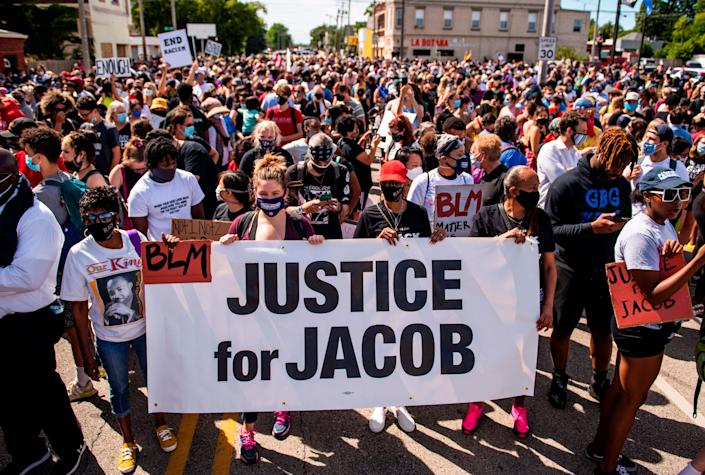 """Protesters march with the family of Jacob Blake during a rally against racism and police brutality in Kenosha, Wisconsin, on August 29, 2020. <p class=""""copyright"""">STEPHEN MATUREN/AFP via Getty Images</p>"""