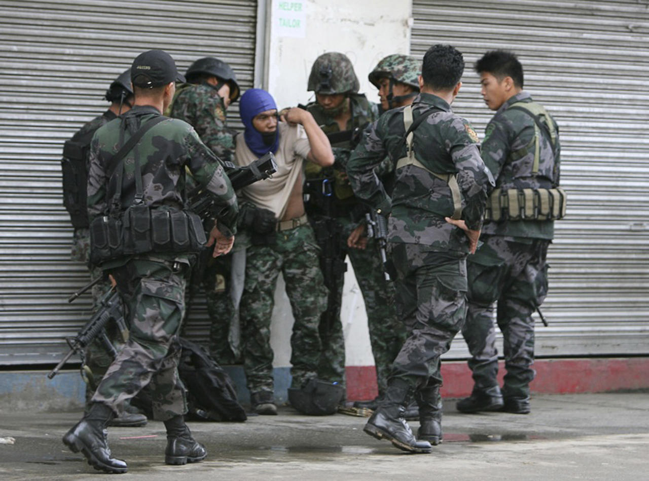 Combat police forces check their comrade who was hit by sniper fire of the MNLF during an encounter in downtown Zamboanga City