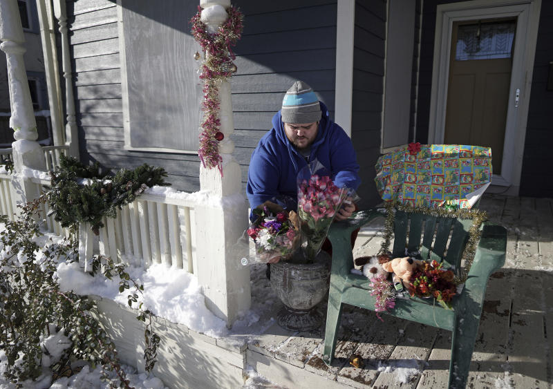 Neighbor Eric Stiver put flowers and stuffed animals on a chair on the porch of the home where a deadly shooting occurred in Minneapolis on Monday, Dec. 2, 2019. Police in Minneapolis haven't yet identified the people who died. (Brian Peterson/Star Tribune via AP)
