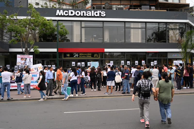 People protest outside a closed McDonald's restaurant, after the the deaths of two teenaged employees, in Lima