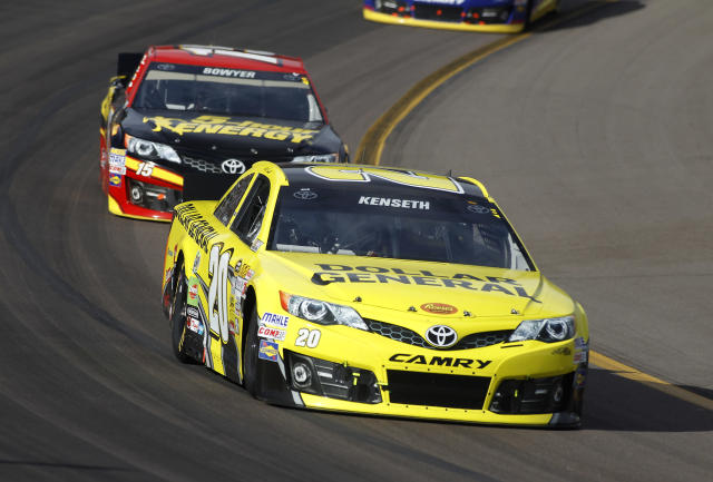 Driver Matt Kenseth (20) leads Clint Bowyer (15) into turn one during the AdvoCare 500 NASCAR Sprint Cup Series auto race at Phoenix International Raceway, Sunday, Nov. 10, 2013 in Avondale, Ariz. (AP Photo/Ralph Freso)