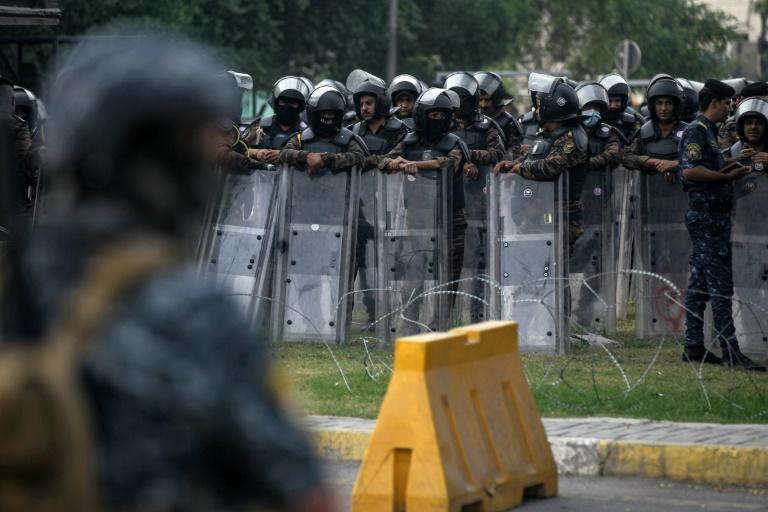 Iraqi riot policemen stand guard during Saturday's demonstration in Baghdad