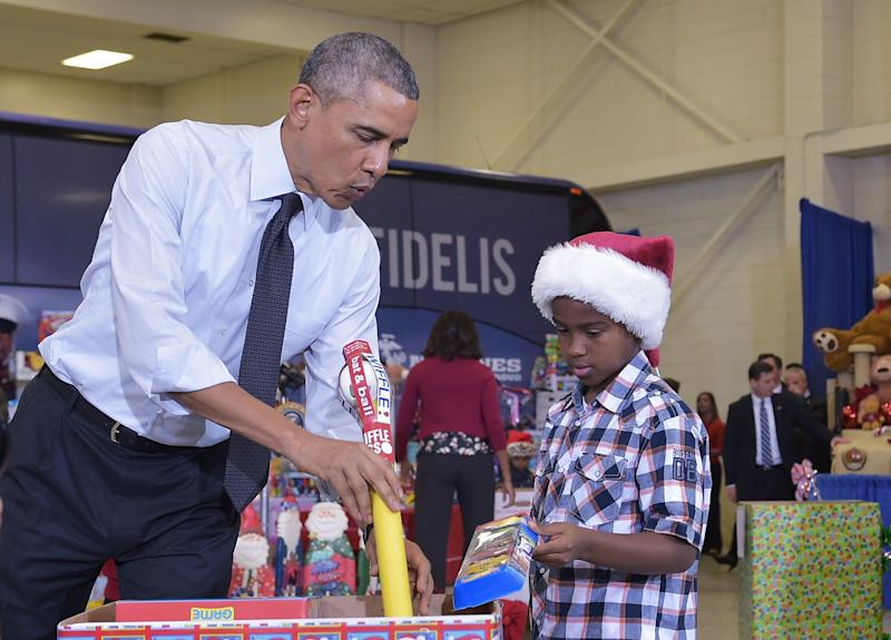 Obama and a young boy sort toys and gifts for the Marine Corps Toys for Tots campaign at Bolling Air Force Base in Washington, D.C., in December 2014. (Photo: MANDEL NGAN via Getty Images)