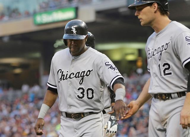Chicago White Sox's Alejandro De Aza (30) and Conor Gillaspie celebrate after they scored on a single by Adam Eaton off Minnesota Twins pitcher Samuel Deduno in the fourth inning of a baseball game on Thursday, July 24, 2014, in Minneapolis. (AP Photo/Jim Mone)