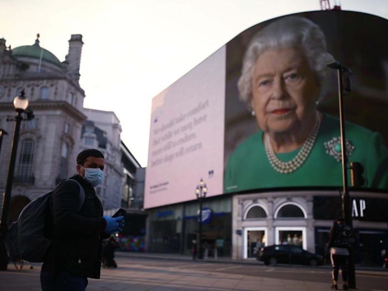 An image of Queen Elizabeth II and quotes from her coronavirus broadcast on Sunday are displayed in London: PA