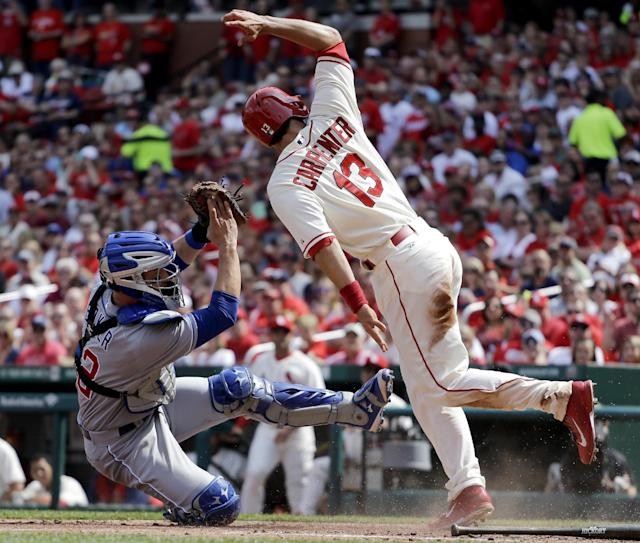 St. Louis Cardinals' Matt Carpenter, right, scores as he avoids the tag from Chicago Cubs catcher John Baker during the fourth inning of a baseball game Saturday, April 12, 2014, in St. Louis. (AP Photo/Jeff Roberson)