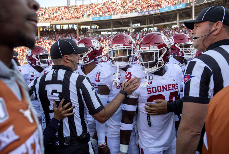 Referees keep Oklahoma players from interacting with Texas players as they leave the field after pregame warmups before an NCAA college football game at the Cotton Bowl, Saturday, Oct. 12, 2019, in Dallas. Oklahoma won 34-27. (AP Photo/Jeffrey McWhorter)