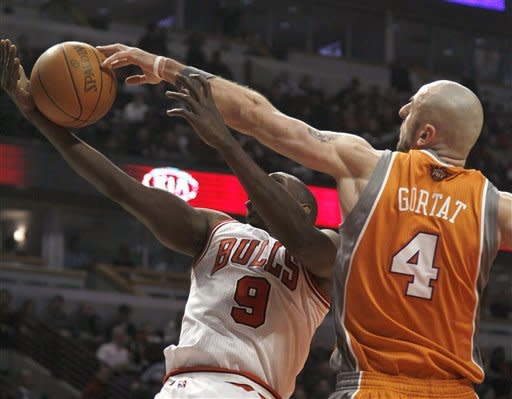 Phoenix Suns center Marcin Gortat (4) fouls Chicago Bulls forward Luol Deng (9 during the first half of an NBA basketball game Tuesday, Jan. 17, 2012, in Chicago. (AP Photo/Charles Rex Arbogast)