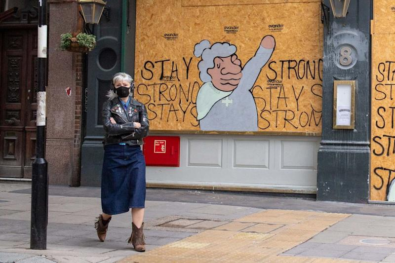 A woman wearing a protective face mask passes a boarded up pub: PA