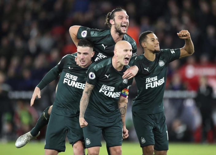 Newcastle United's Jonjo Shelvey, centre below, celebrates with teammates after scoring his side's second goal of the game against Sheffield United, during their English Premier League soccer match at Bramall Lane in Sheffield, England, Thursday Dec. 5, 2019. (Danny Lawson/PA via AP)