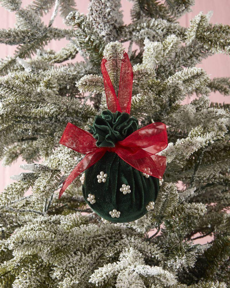 """<p>Elegant and so simple, this DIY only takes 4 supplies to complete.</p><p><strong>To make:</strong> Cut a square of velvet fabric. Wrap around a ball ornament, cinching it at the top. Tie a piece of ribbon around the cinch to hold closed and create a hanger. Tie a bow from the same ribbon and attach with hot glue. Attach small pearl craft bead with hot glue.</p><p><a class=""""link rapid-noclick-resp"""" href=""""https://www.amazon.com/Kanzueri-Bracelet-Necklaces-Jewelry-Repairing/dp/B091F3WXB5/ref=sr_1_6?tag=syn-yahoo-20&ascsubtag=%5Bartid%7C10050.g.1070%5Bsrc%7Cyahoo-us"""" rel=""""nofollow noopener"""" target=""""_blank"""" data-ylk=""""slk:SHOP SMALL PEARL BEADS"""">SHOP SMALL PEARL BEADS</a></p>"""