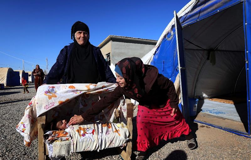 A woman from Mosul tends to her baby at the al-Khazar camp on November 25, 2016 (AFP Photo/Safin Hamed)