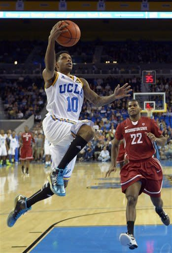 UCLA guard Larry Drew II, left, puts up a shot in front of Washington State guard Royce Woolridge during the first half of their NCAA college basketball game, Saturday, Feb. 9, 2013, in Los Angeles. (AP Photo/Mark J. Terrill)