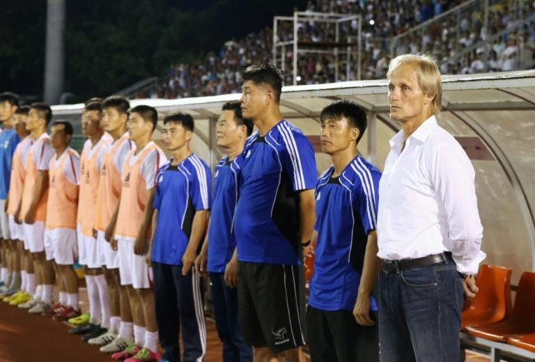 North Korea's coach Jørn Andersen (R) stands next to officials and players ahead of a friendly match in Ho Chi Minh City, in October 2016