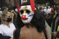 """A protestor wears a mask on the back of her head which says """"no"""" in French as she attends a demonstration in Paris, France, Saturday, July 31, 2021. Demonstrators gathered in several cities in France on Saturday to protest against the COVID-19 pass, which grants vaccinated individuals greater ease of access to venues. (AP Photo/Adrienne Surprenant)"""