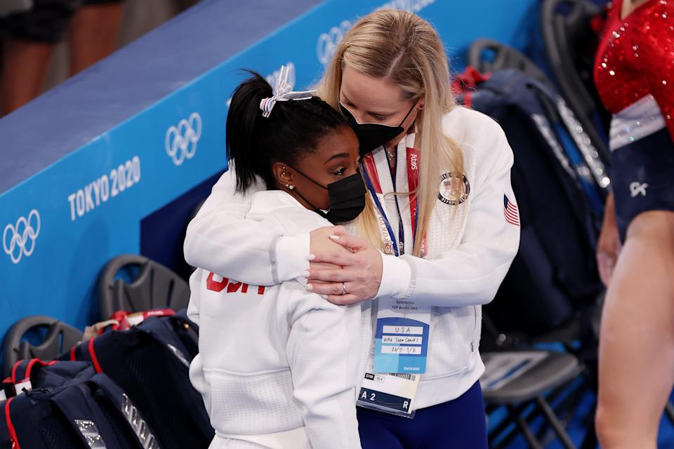 TOKYO, JAPAN - JULY 27: Simone Biles of Team United States is embraced by coach Cecile Landi during the Women's Team Final on day four of the Tokyo 2020 Olympic Games at Ariake Gymnastics Centre on July 27, 2021 in Tokyo, Japan. (Photo by Jamie Squire/Getty Images)
