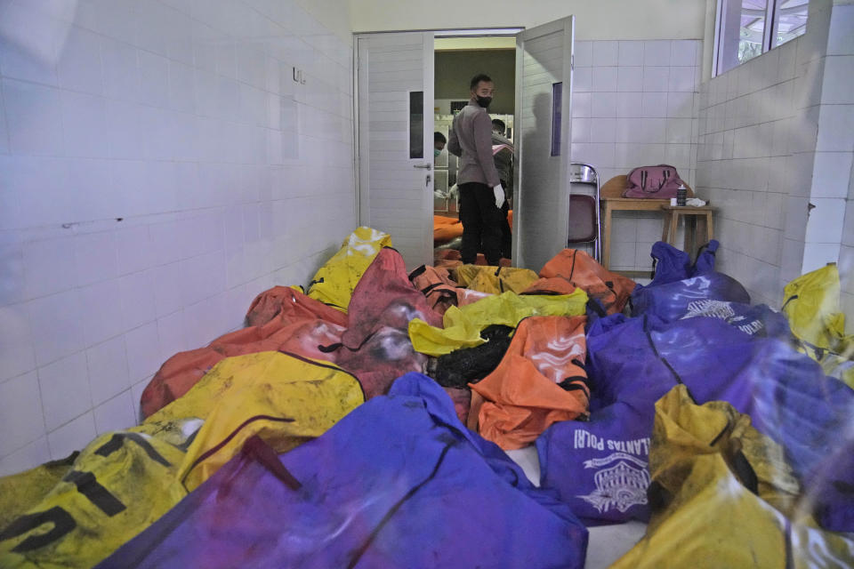 A police officer stands near body bags containing the bodies of the victims of a prison fire at the local hospital's morgue in Tangerang on the outskirts of Jakarta, Indonesia, Wednesday, Sept. 8, 2021. A massive fire raged through an overcrowded prison near Indonesia's capital early Wednesday, killing a number of inmates. (AP Photo/Dita Alangkara)