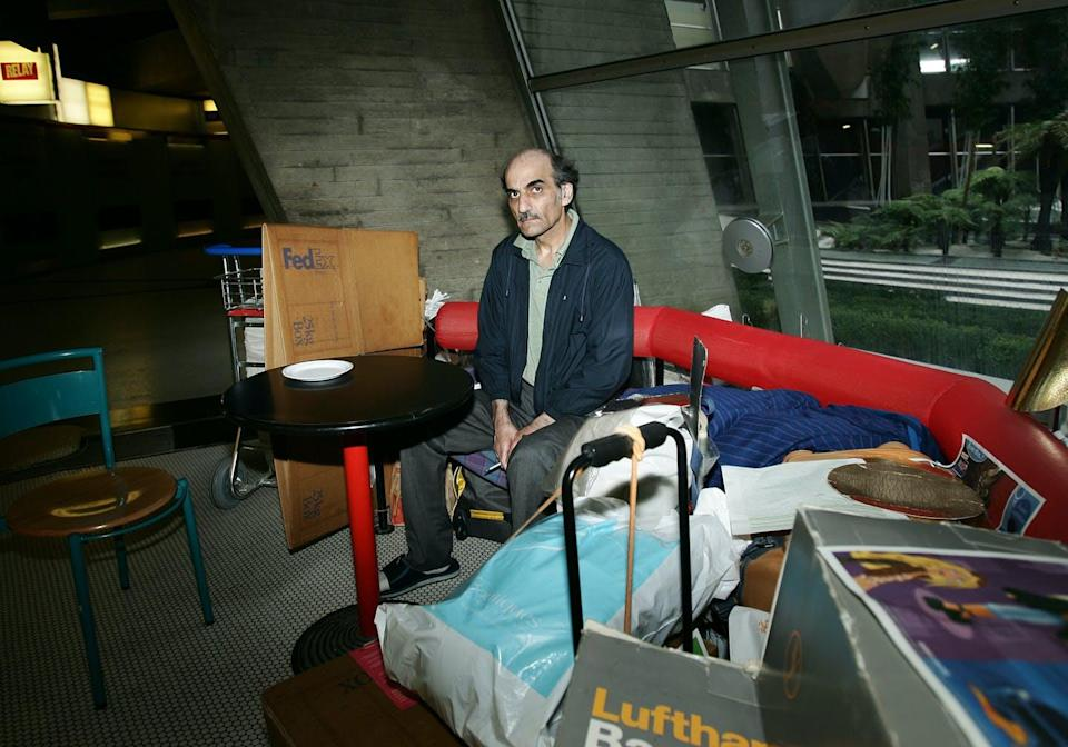 """<span class=""""caption"""">Mehran Karimi Nasseri sits among his belongings in a 2004 photograph taken at Charles de Gaulle Airport, where he lived for nearly 18 years.</span> <span class=""""attribution""""><a class=""""link rapid-noclick-resp"""" href=""""https://www.gettyimages.com/detail/news-photo/sir-alfred-mehran-59-years-old-originally-from-iran-has-news-photo/627630152?adppopup=true"""" rel=""""nofollow noopener"""" target=""""_blank"""" data-ylk=""""slk:Eric Fougere/VIP Images/Corbis via Getty Images"""">Eric Fougere/VIP Images/Corbis via Getty Images</a></span>"""