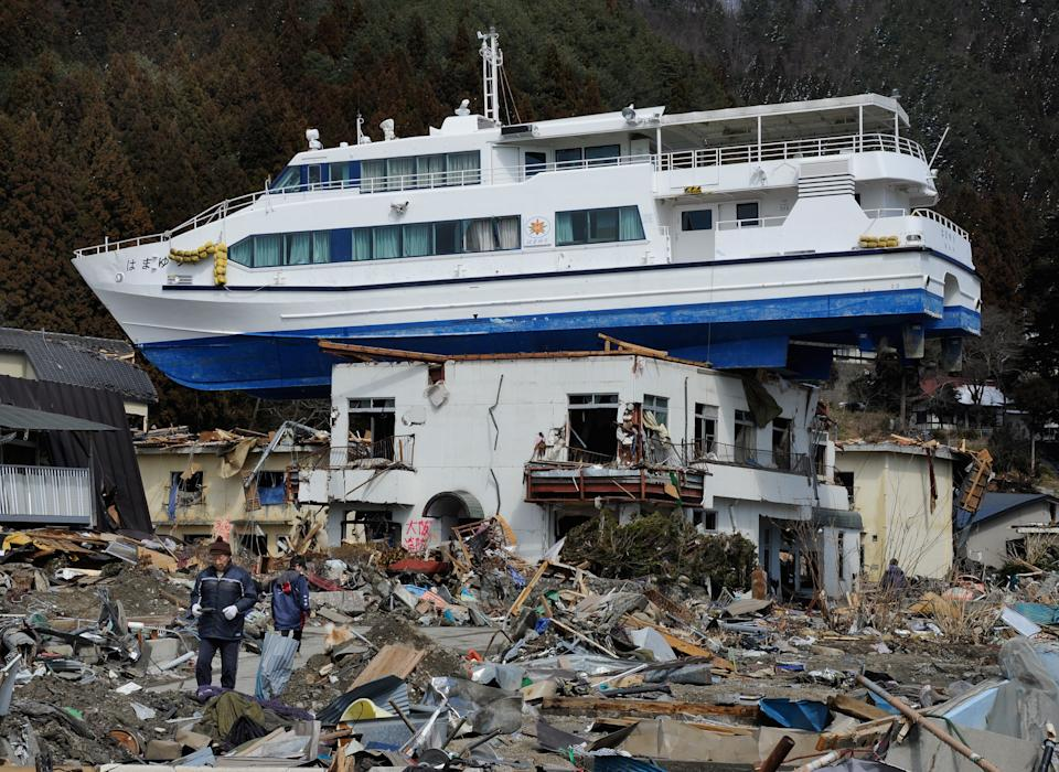 <p>FILE PHOTO: A cruise ship lies on the roof of a two storey building in Otsuchi, Iwate Prefecture, on March 24, 2011, after the recent earthquake and tsunami disaster. (Photo: TORU YAMANAKA/AFP via Getty Images)</p>