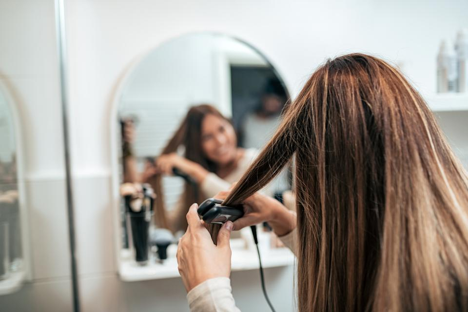 Rear view of young woman straightening hair with straightener.