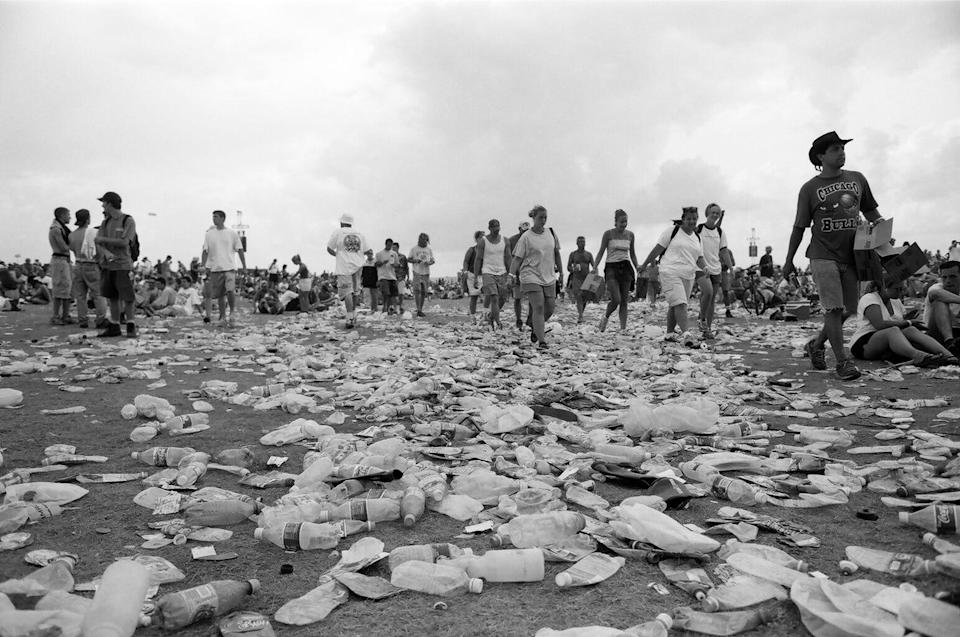 Woodstock 99 attendees walk along piles of trash at Griffiss Air Force Base in Rome, New York.
