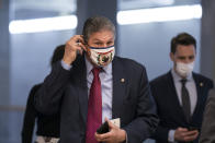 Sen. Joe Manchin, D-W.Va., adjusts his face mask as he arrives for votes on Biden administration nominees, at the Capitol in Washington, Tuesday, March 16, 2021. (AP Photo/J. Scott Applewhite)