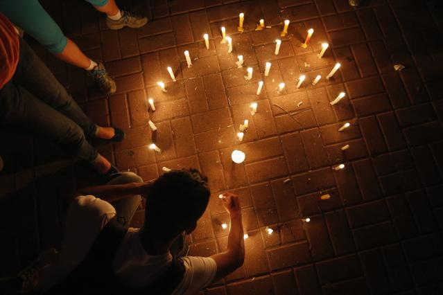 An anti-government protester places candles to form a peace sign during a rally against violence in Caracas March 7, 2014. Latin American foreign ministers will meet next week to discuss the unrest in Venezuela that has left at least 20 dead and convulsed the South American OPEC nation, diplomatic sources said on Friday. REUTERS/Tomas Bravo (VENEZUELA - Tags: POLITICS CIVIL UNREST)
