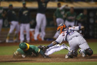 Oakland Athletics' Ramon Laureano, left, slides to beat the tag of Houston Astros catcher Martin Maldonado during the ninth inning of a baseball game Friday, Aug. 17, 2018, in Oakland, Calif. (AP Photo/Ben Margot)