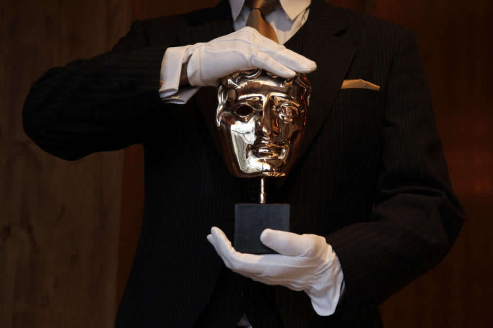 A British Academy of Film and Television Arts (BAFTA) award mask is displayed by an employee during a media viewing at the Savoy Hotel in London February 8, 2012. The BAFTA awards ceremony will take place on Sunday.   REUTERS/Stefan Wermuth (BRITAIN - Tags: ENTERTAINMENT SOCIETY)