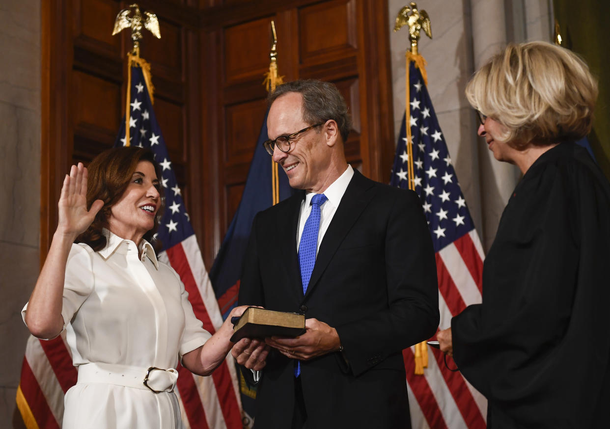New York Chief Judge Janet DiFiore swears in Kathy Hochul as the first woman to be New York's governor while her husband Bill Hochul holds a bible during a ceremonial swearing-in ceremony at the state Capitol, Tuesday, Aug. 24, 2021, in Albany, N.Y. (AP Photo/Hans Pennink)