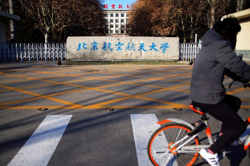 FILE PHOTO: A person rides a bicycle past an entrance of Beihang University in Beijing