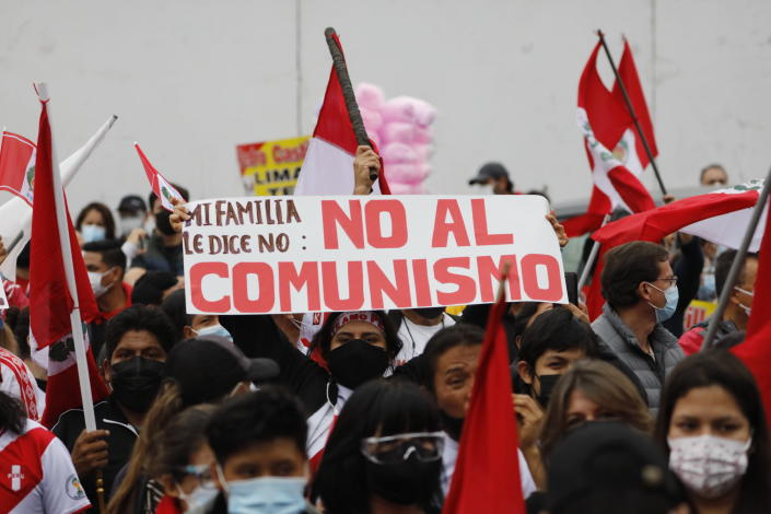 """A supporter of presidential candidate Keiko Fujimori holds up a sign with a message that reads in Spanish: """"My family says, No to Communism"""" during a protest against alleged election fraud, in Lima, Peru, Saturday, June 12, 2021. Supporters are hoping to reverse the results of the June 6th presidential runoff election that seem to have given the win to opponent Pedro Castillo amid unproven claims of possible vote tampering. (AP Photo/Guadalupe Pardo)"""