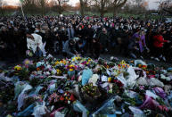 People gather, at the band stand in Clapham Common, in memory of Sarah Everard, after an official vigil was cancelled, in London, Saturday, March 13, 2021. A serving British police officer accused of the kidnap and murder of a woman in London has appeared in court for the first time. Wayne Couzens, 48, is charged with kidnapping and killing 33-year-old Sarah Everard, who went missing while walking home from a friend's apartment in south London on March 3. (AP Photo/Frank Augstein)